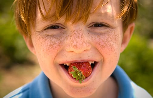 Kid smiling eating a strawberry in Byron Georgia