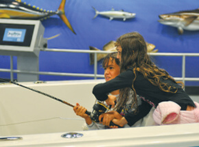 Kids enjoying the fishing and boating simulator at Go Fish Education Center in Byron Georgia